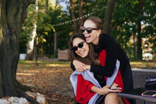 Niña abrazando a su amiga. retrato dos novias en el parque.
