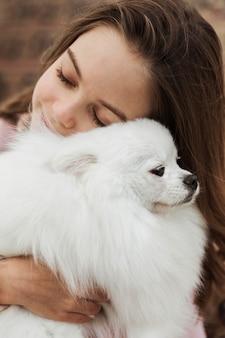 Niña abrazando a su cachorro esponjoso