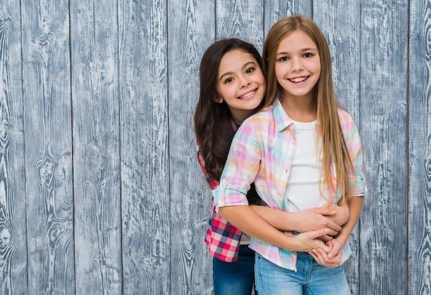 Niña abrazando a su mejor amiga por detrás, de pie contra la pared de madera gris