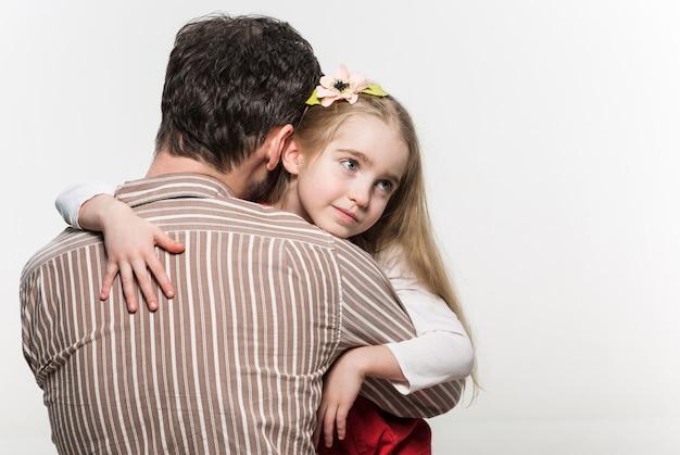 Niña abrazando a su padre sobre un blanco