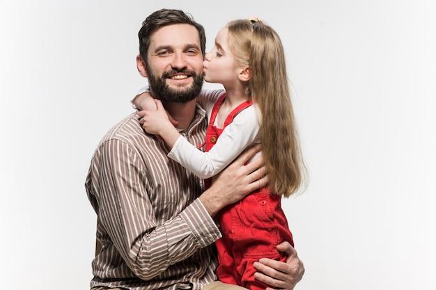 Niña abrazando a su padre sobre una pared blanca