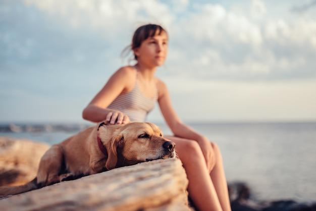 Niña abrazando a su perro mientras está sentado en la roca junto al mar
