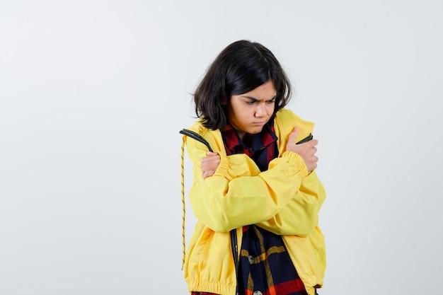 Niña abrazándose a sí misma en camisa a cuadros, chaqueta y luciendo linda vista frontal.