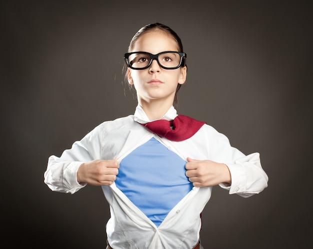 Niña abriendo su camisa como un superhéroe