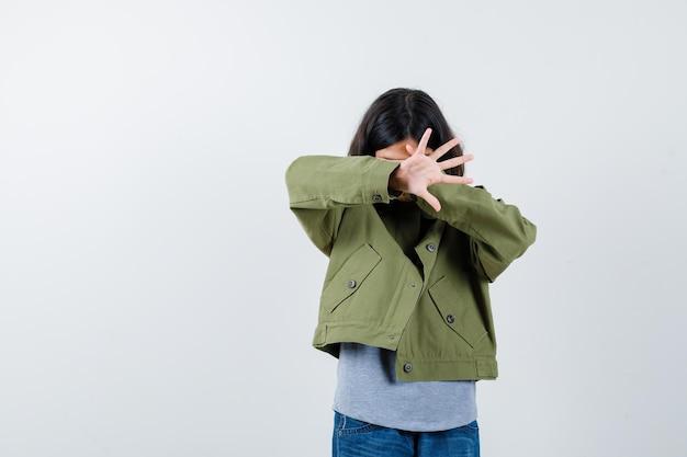 Niña con abrigo, camiseta, jeans cubriendo los ojos con la mano, mostrando la palma y mirando asustada, vista frontal.