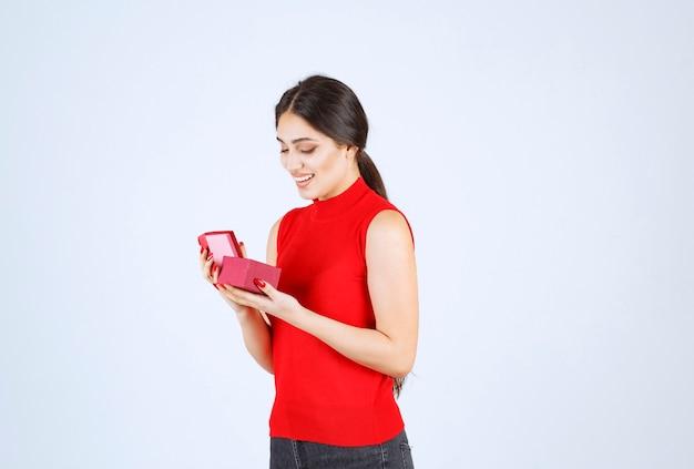 La niña abrió una caja de regalo roja y se siente feliz.
