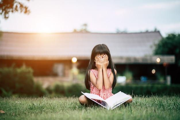 Niña aburrida leyendo en el jardín de la casa