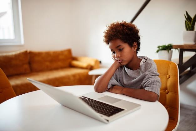 Niña aburrida que mira la computadora portátil en casa.