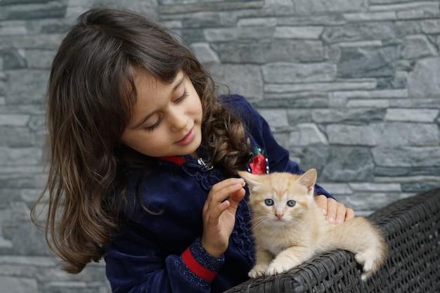 Una niña acaricia un gatito marrón