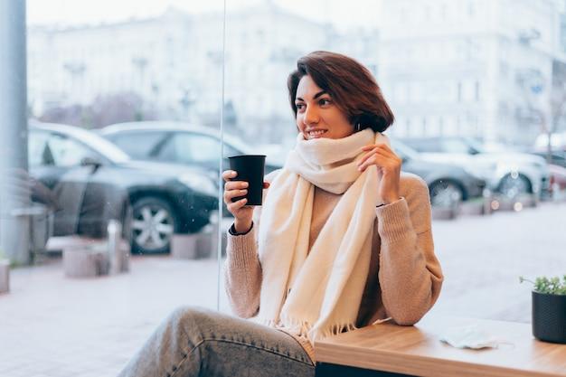 Una niña en un acogedor café se calienta con una taza de café caliente.