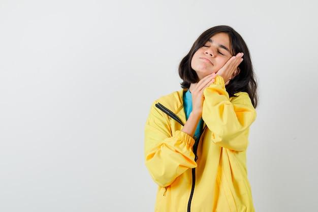 Niña acolchando la cara en sus manos en camisa, chaqueta y mirando soñolienta, vista frontal.