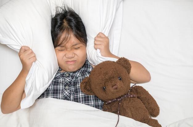 Niña acostada en la cama cubriendo la cabeza con la almohada porque un ruido molesto demasiado fuerte. niño irritado que sufre de vecinos ruidosos, tratando de dormir después de la señal de despertador de alarma