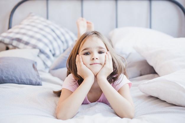 Niña acostada en la cama, niña descansando entre las almohadas y las mantas, sueños