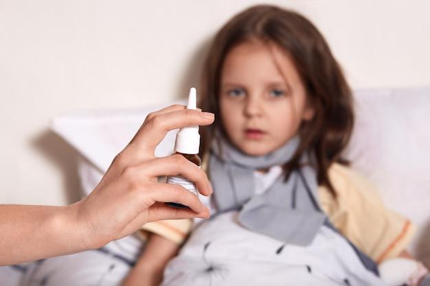 Niña acostada en la cama, su madre trata su nariz que moquea con spray nasal, niña de cabello oscuro mirando a la cámara