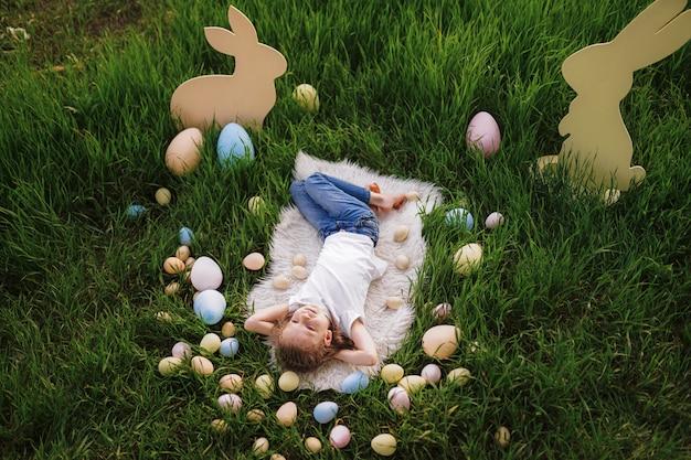 Niña acostada con huevos en vacaciones de pascua