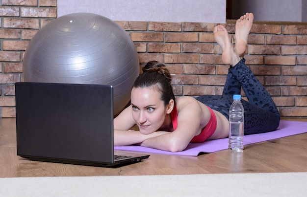 Niña acostada con las manos debajo de mi cabeza en la estera de yoga y mira la pantalla del portátil. fitness en casa