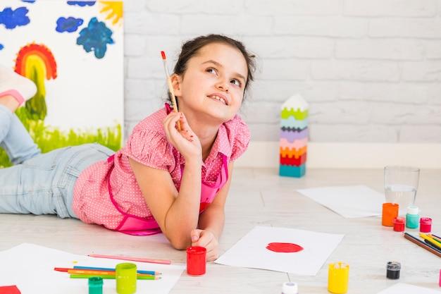 Niña acostada en el piso mirando hacia arriba mientras pinta sobre papel