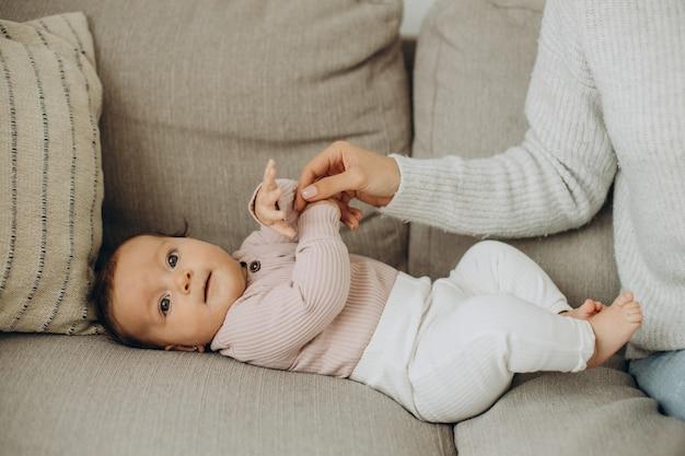Niña acostada en el sofá cerca de su madre