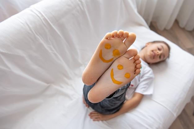 Una niña está acostada en un sofá con los pies pintados con pinturas. Foto gratis