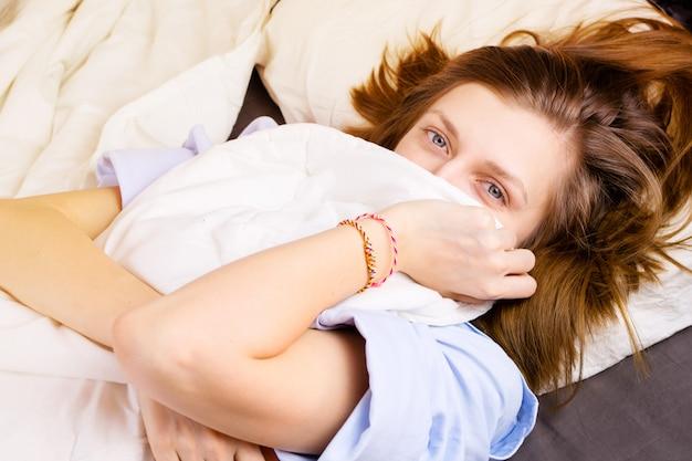Niña acostada en su cama, la cara cubierta por una manta sonriendo con los ojos. , concepto de sueño matutino o nocturno.