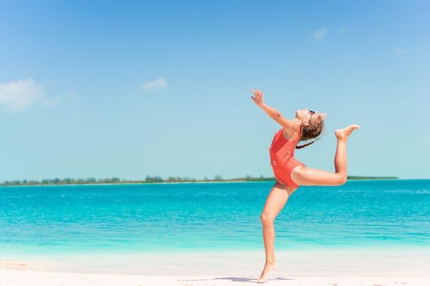 Niña activa en la playa divirtiéndose mucho en la orilla dando un salto