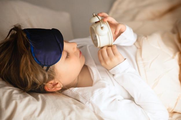 La niña se acuesta en la cama por la mañana y mira el reloj despertador.