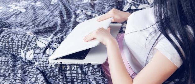 La niña se acuesta en la cama y usa una computadora portátil.