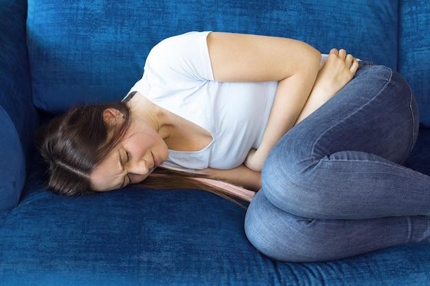 La niña se acuesta en el sofá con dolor abdominal intenso, dolor durante la menstruación en una mujer