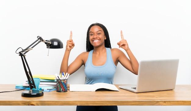 Niña adolescente afroamericana con cabello largo trenzado en su lugar de trabajo que apunta una gran idea