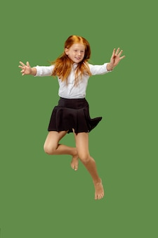 Niña adolescente caucásica feliz saltando en el aire, aislado sobre fondo verde de estudio.