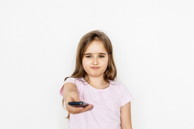 Una niña, una adolescente con un control remoto desde el televisor, cambia de canal, busca una caricatura, no está contenta, una prohibición de ver, niños y adultos, televisión e internet, entretenimiento