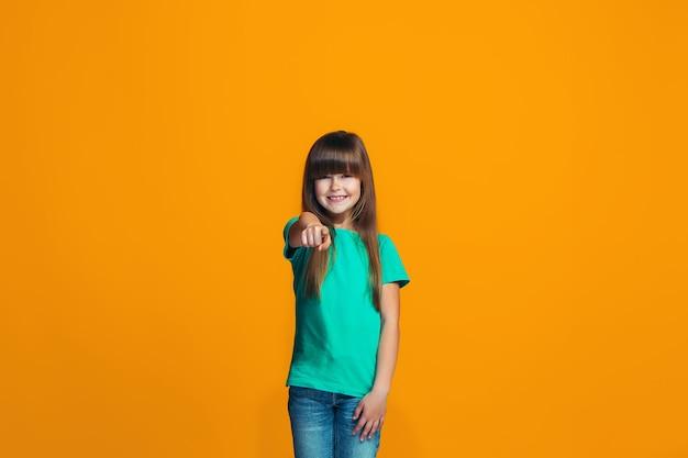 La niña adolescente feliz apuntando a usted, retrato de detalle de media longitud en espacio naranja.