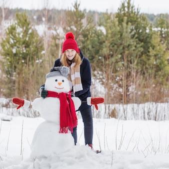 Niña adolescente feliz con muñeco de nieve en bosque de invierno