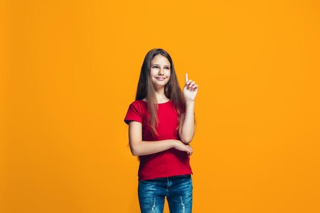 La niña adolescente feliz de pie y sonriendo contra el espacio naranja.