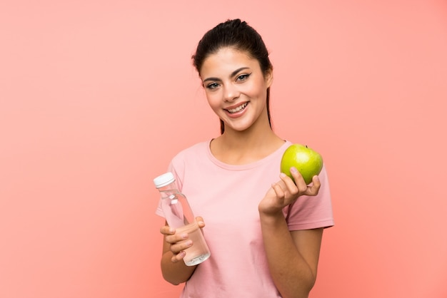 Niña adolescente feliz sobre pared rosa aislado con una botella de agua y una manzana