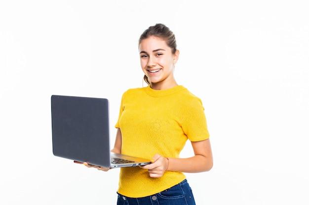 Niña adolescente linda sonriente que usa la computadora portátil sobre la pared blanca