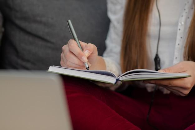 Niña adolescente sonriente con auriculares escuchando audio curso tomando notas, joven aprendiendo idiomas extranjeros, autoeducación digital, estudiando en línea, disfrutando de la música.