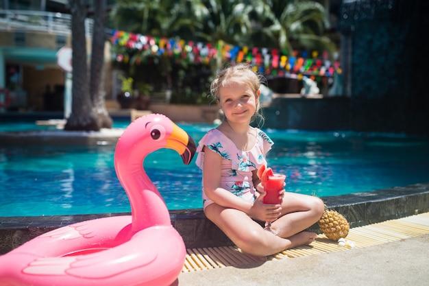 Niña adorable con el anillo inflable del flamenco rosado que bebe el jugo fresco de la sandía