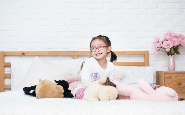 La niña adorable asiática se sienta en la cama entre muchas muñecas lindas con feliz