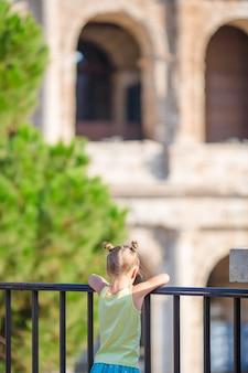 Niña adorable delante del colosseum en roma, italia.