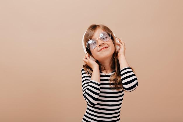 Niña adorable divertida con gafas y vestido despojado disfrutando de la música en los auriculares con una sonrisa y los ojos cerrados
