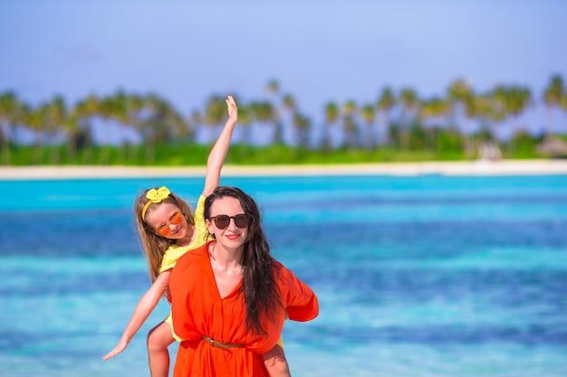 Niña adorable y feliz mamá divirtiéndose durante vacaciones en la playa