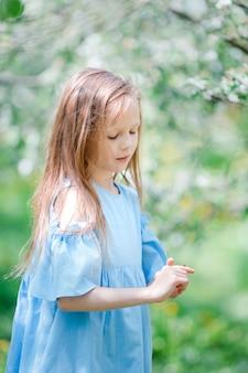 Niña adorable en jardín floreciente de apple en el hermoso día de primavera