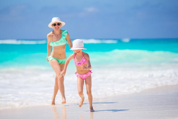 Niña adorable y joven madre en playa tropical