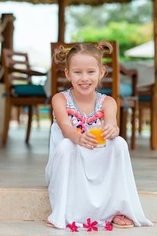Niña adorable con el jugo en el café al aire libre