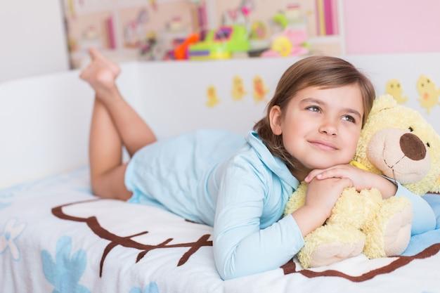 Niña adorable linda en el dormitorio abrazando oso de peluche