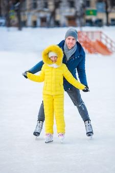 Niña adorable con padre aprendiendo a patinar en pista de hielo