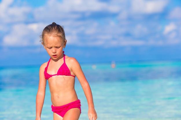 Niña adorable en la playa durante las vacaciones de verano