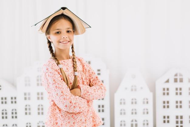 Niña adorable posando feliz con un libro