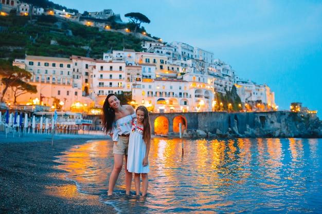 Niña adorable en puesta del sol en la ciudad de amalfi en italia